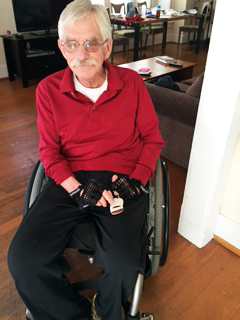 man in wheelchair pushes button on remote device to open front door