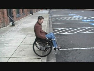 manual wheelchair using using a wheelie to propel down a curb.