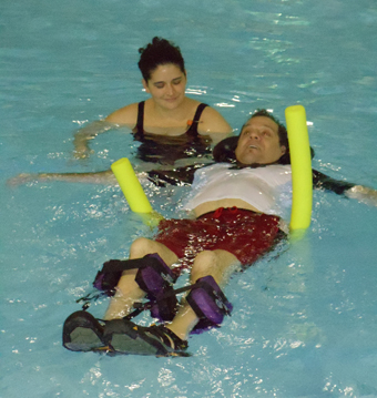 Individual with spinal cord injury floats in pool with an able-bodied assitant.