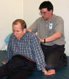 Figure 2: Physical therapist Dave Colescott takes several measurements, including hip width, back length and leg length, to ensure a proper fit for Hennig's new wheelchair.