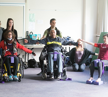 people in wheelchairs do arm stretches in yoga class